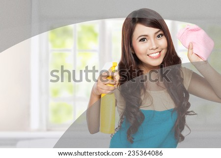 portrait of Attractive young woman cleaning windows in the house - stock photo