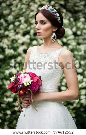 Portrait of attractive young woman in color crown , sweet and sensual, with flowers on background of roses. Near the wall of the flower.