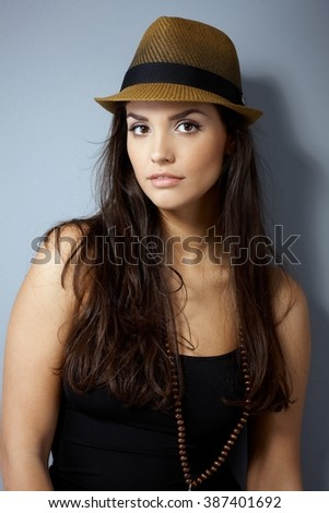 Portrait of attractive young woman in straw hat with long hair, looking at camera. - stock photo