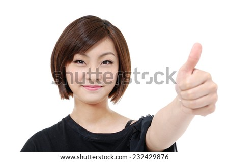 Portrait of attractive young woman laughing at camera with thumbs up. - stock photo