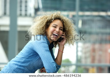 Portrait of attractive young woman laughing on telephone call