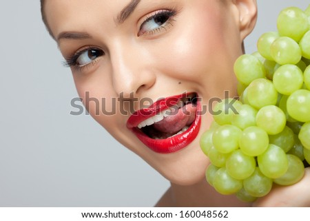 Portrait of attractive young woman licking lips and looking at bunch of green grapes, studio background. - stock photo
