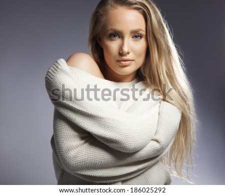 Portrait of attractive young woman looking at a camera. Caucasian young female model posing against grey background. - stock photo