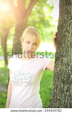 portrait of attractive young woman, on a background summer park