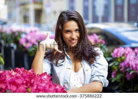 Portrait of attractive young woman on open air. Woman making a call me sign outdoors  - stock photo