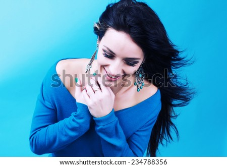 Portrait of attractive young woman over blue background. Glamour fashion woman portrait. Studio photography. Portrait of a beautiful brunette. - stock photo