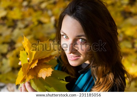 Portrait of attractive young woman sitting on a carpet of yellow fallen leaves.