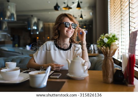 Portrait of attractive young woman smiling charmingly while looking out the window for her friends just arrived to the coffee shop where they meet,gorgeous female enjoying recreation time at breakfast - stock photo