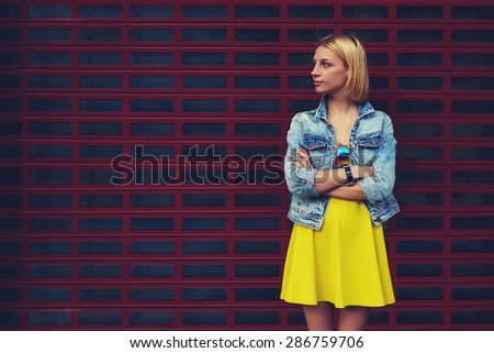 Portrait of attractive young woman standing on blank copy space background for your text message or content, stylish female looking to the space for your promotion or publicity information, filter - stock photo