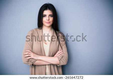 Portrait of attractive young woman with arms folded standing over gray background. Looking at camera - stock photo