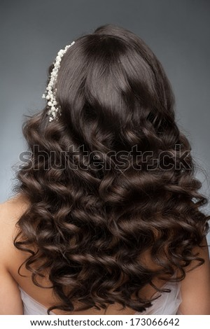 Portrait of attractive young woman with beautiful bridal hairstyle and stylish hair accessory. Brunette with long curly hair, rear view