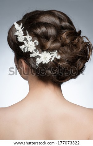 Portrait of attractive young woman with beautiful hairstyle and stylish hair accessory, rear view - stock photo