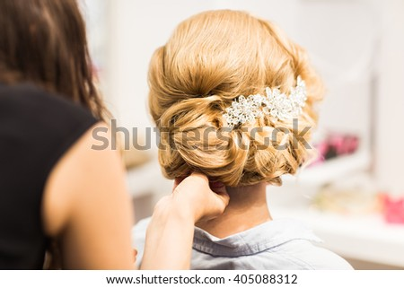 Portrait of attractive young woman with beautiful hairstyle and stylish hair accessory, rear view. - stock photo