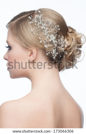 Portrait of attractive young woman with beautiful hairstyle and stylish hair accessory, side view - stock photo