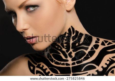 Portrait of attractive young woman with black body art on black background - stock photo