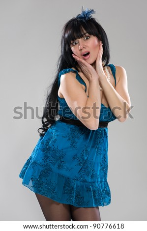 Portrait of attractive young woman with long hair in beautiful blue dress posing in studio on gray background - stock photo