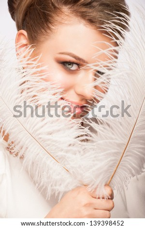 Portrait of attractive young woman with makeup holding ostrich feather