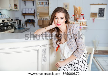 Portrait of attractive young woman with red lips sitting in cafe - stock photo
