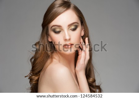 Portrait of attractive young woman with stylish bright makeup and long curly hair - stock photo