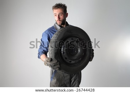 Portrait of auto mechanic holding a  wheel  isolated on a white background - stock photo