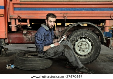 Portrait of auto mechanic in his workshop - stock photo