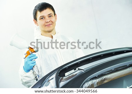 portrait of automobile repairman painter in protective workwear with spray gun in his hand - stock photo