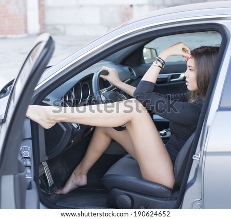 Portrait of babe Young adult sexy brunette dreaming girl sitting in luxury black car Slim cute asian woman inside black leather chair auto open door with leg With reflection on window Fingers on lips - stock photo