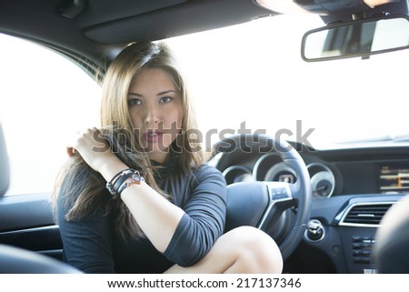 Portrait of babe Young adult sexy brunette dreaming girl sitting in luxury black car Slim cute asian woman inside black leather chair auto open door with leg With reflection on window Fingers on lips