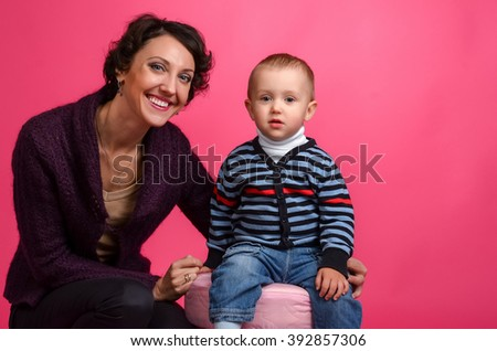 Portrait of  baby and his mother on a pink background - stock photo