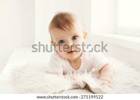 Portrait of baby at home in white room near window - stock photo