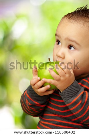 Portrait Of Baby Boy Eating Green Apple against a nature background - stock photo