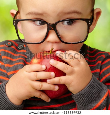 Portrait Of Baby Boy Eating Red Apple against a nature background - stock photo