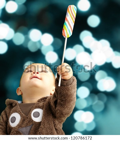 Portrait Of Baby Boy Holding Lollipop against a background of shiny blue lights - stock photo