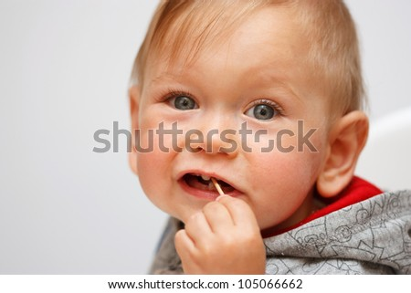 Portrait of Baby boy with toothpick in mouth - stock photo