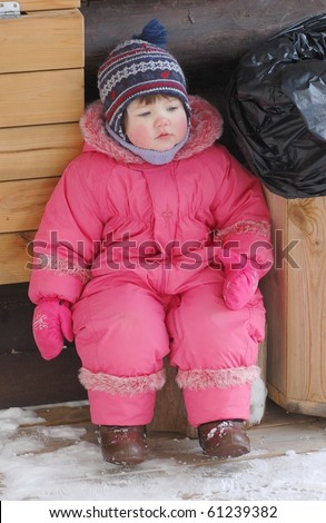 Portrait of baby by the trash bag in winter time - stock photo