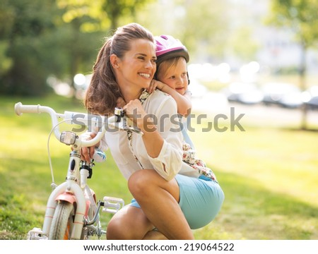 Portrait of baby girl hugging mother near bicycle in park - stock photo