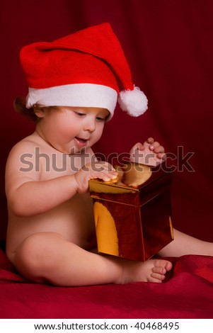 portrait of baby in red hat with gift - stock photo