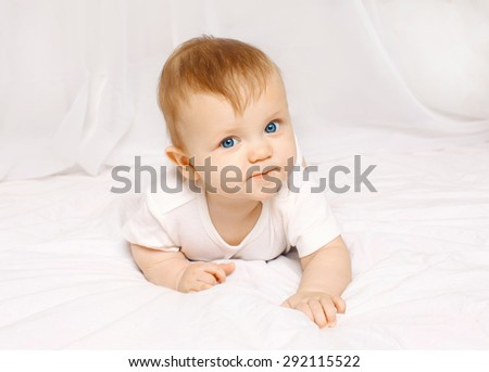 Portrait of baby lying on the bed at home closeup - stock photo