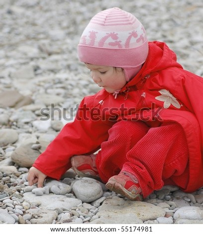 Portrait of baby on pebble stones by the sea - stock photo