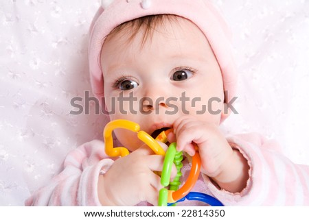 Portrait of Baby with vibrant chain toy wearing hat