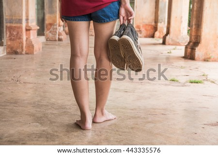 Portrait of barefoot, woman with shoes in hand.