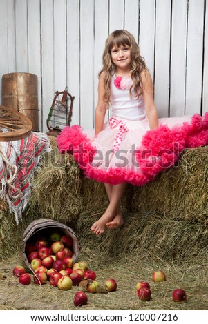 Portrait of barefooted funny little blond girl villager dressed luxuriant wavy ball dress with frill sitting on haystack near inverted pail with apples in wooden vintage hayloft - stock photo
