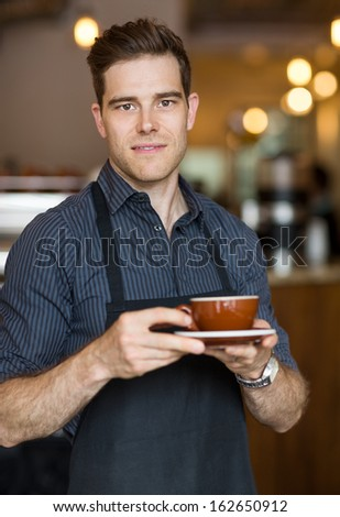 Portrait of barista holding cappuccino cup in cafe - stock photo