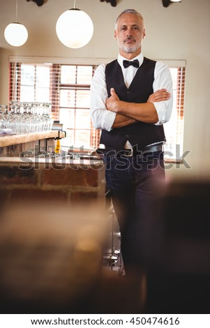 Portrait of bartender standing with arms crossed at bar counter