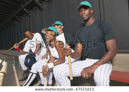Portrait of baseball team in dugout - stock photo