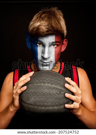 portrait of basketball player with french flag painted on his face - stock photo