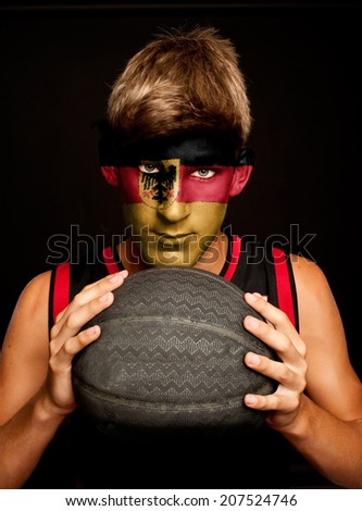 portrait of basketball player with german flag painted on his face - stock photo