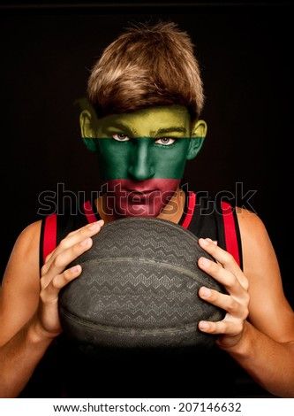portrait of basketball player with lithuanian flag painted on his face - stock photo