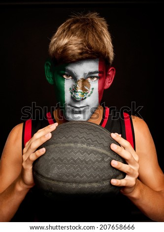 portrait of basketball player with mexican flag painted on his face - stock photo
