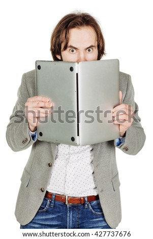 portrait of bearded business man hiding behind his laptop computer in his hands. emotions, facial expressions, feelings, body language, signs. image on a white studio background.